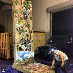 Alec Monopoly painting a piece of the Berlin Wall