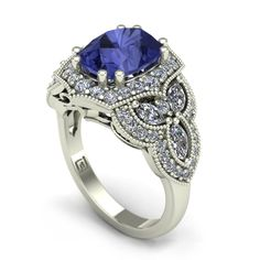 This gorgeous statement ring features a vintage style design with a blue-violet cushion-cut tanzanite set in 14k white gold. The center stone is surrounded by diamonds and flanked by a trio of marquis