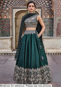Beautifully embroidered with our signature craft Gota Patti, the Vatsala Lehenga sparkles with every step you take. The emerald green silk lehenga is perfect for any royal occasion. Style Tip: Pair this beautiful lehenga with jadau chand b Indian Gowns Dresses, Indian Fashion Dresses, Dress Indian Style, Indian Designer Outfits, Indian Skirt, Indian Designers, Designer Dresses, Indian Lehenga, Green Lehenga