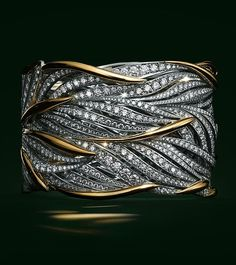 Flowing gold and platinum leaves twist around the wrist, accentuated with brilliant diamonds.