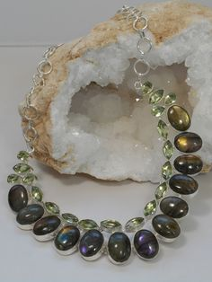 A one-of-a-kind gorgeous hand-polished cabachon Labradorite necklace with 13 highly chatoyant Labradorite gemstones, adorned with 19 vibrant faceted Green Amethyst gemstones, set in 925-hallmarked ste