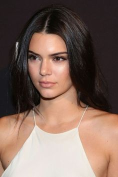 Kendall Jenner displays her nipple piercing in a slinky white dress