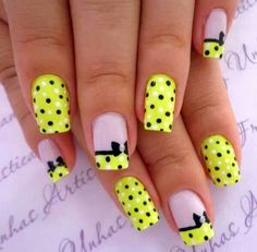 Adorable black, yellow and white bow nail art design. Coat your nails in cute black and white polka dots with a yellow background while painting a bow underneath your polka dot French tips.