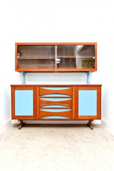 This is a bar from the 1950′s which we tried to keep as original as possible. It has an upper display cabinet attached to the base. The bottom has 3 pull out drawers and 2 push cabinets. We wanted to keep it entirely wood, but after many attempts to save the wood we had to paint the insets a nice, mod blue. This is one big piece and it is completely finished in the back. It is a really special piece of furniture. Perfect for you mid century modern freaks out there! $1300