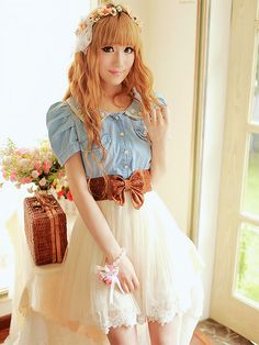 A cute combination of a denim shirt with a brown bow belt and the white skirt.
