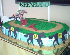 Horse racing - The cake is covered with Buttercream, the sign is pastillage and the jockey is a edible photo on fondant. The horses are made of fondant also
