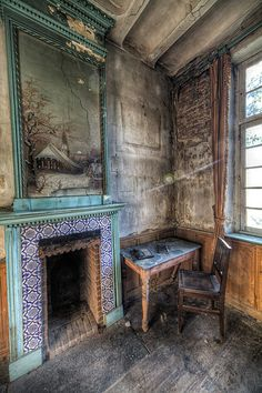 An ornate fireplace in a decaying interior.