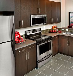 Warm Brown Kitchen Cabinets With Stainless Steel Appliances, With Green  Tile Backsplash And Grey Tile Floor. At Sandstone By Avi Urban.
