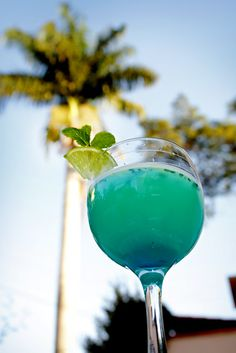 • 2 parts of fresh orange juice • 1 part of lime juice (with water and sugar) • 1 part of rum • 1/2 part of Curaçao Bleu • Chopped mint • A bit of sugar • A little bit more of Curaçao Bleu, to give a blue touch at the bottom of the cup • Ice
