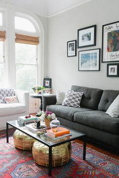 living room: light gray walls, dark gray couch, pops of color.