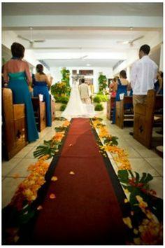 Hojas verdes grandes llamadas monsteras con pétalos de rosas en naranja y rojo, todo esto colocado en la orilla de la alfombra.