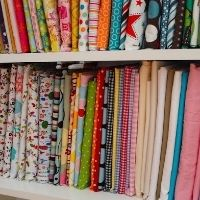 Many miniature bolts of fabric organized on a book shelf