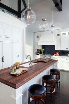 Cook's kitchen features black truss ceilings over white shaker cabinets paired with white marble countertops and a black subway tiled backsplash.