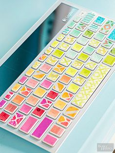 Work doesn't have to be mundane when you have a rainbow at your fingertips. To cover your keyboard's keys with washi tape, lay transparent glossy paper over the keyboard and trace the keys onto the paper. Adhere washi tape to the tracings, trim the excess, remove the tape, and press onto the keys.