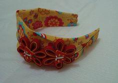 Tiara faixa em tecido algodão, com flores de viés e botões decorativos de borboletas. Para crianças a partir de 2 anos. R$ 9,90
