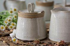 Se hace esta hermosa mano lanza tazón de azúcar blanco de cerámica con una arcilla moteada. El cuerpo y la tapa están recubiertos de un esmalte blanco. El elegante soporte de la tapa da la taza un aspecto único y elegante. Hay un pequeño recorte en la tap