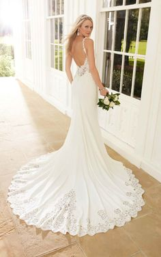 This sheath wedding dress from Martina Liana boasts lace appliques with pearl and Diamante embellishments and illusion-lace sides and back. The Bellagio crepe skirt has lace detailing and beading on its train. The back zips up under pearl beading.