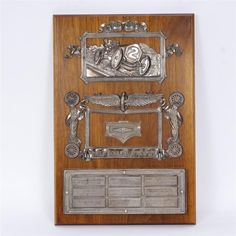 The Prest-O-Lite Trophy, first presented at the 1909 Indianapolis Motor Speedway; The Prest-O-Lite Trophy, first presented at the 1909 Indianapolis Motor Speedway 250 mile Prest-O-Lite 250 mile feature race, won by Bob Burman; Composed of the cast silver feature mountings from the original composition, which may have originally been afixed to a brick form, now mounted on a wooden plaque.<br><br>Nine engraved silvered plaques commemorate winners and various driving accomplishments...