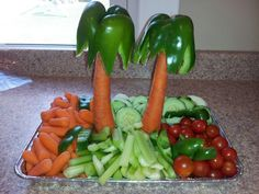 Tropical veggie tray. Green pepper and carrot palm trees. Cut a potato in half and place flat side down.  Use a toothpick to attach the carrot to the potato to stand the palms on their own. I cut hole in potato for carrot then use toothpick.  I use fruit, cheese, veggies.