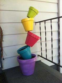 "Staggered ""Tipsy"" Flower Pots - use 12"" pot on bottom w/various sizes staggering up. Use preferred length of rebar allowing for at least two feet in ground. Use as many pots you'd like for however tall you'd like it."