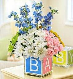Baby Block Cube- carnations, poms and delphinium, accented with fresh leather leaf in a clear glass cube vase wrapped with a colorful ribbon with the letters B-A-B-Y $44.99- $54.99 #newbaby #babygifts #baby