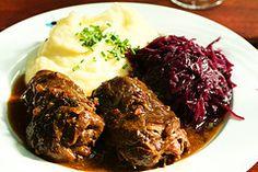 """<b>Rouladen+(1)</b>:+Roulade+ist+ein+deutsches+Fleischgericht+aus+Speck,+Zwiebel,+Senf+und+eingelegtem+Gemüse,+eingerollt+in+ein+dünn+geschnittenes+Stück+Rindfleisch+und+dann+gekocht.+In+manchen+Ländern+ist+Roulade+als+""""Beef+Olive""""+(""""Rindsolive"""")+bekannt."""