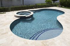 This lakeside pool shimmers with StoneScapes Aqua Blue Touch of Glass finish. - This lakeside pool shimmers with StoneScapes Aqua Blue Touch of Glass finish. The kidney shape seem - Swimming Pools Backyard, Pool Decks, Pool Landscaping, Kidney Shaped Pool, Pool Pavers, Florida Pool, Pool Finishes, Pool Remodel, Pool Installation