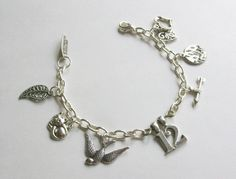 The Hunger Games charm bracelet mockingjay district 12 arrow fire inspired by The Hunger Games movie and books. $17.00, via Etsy.