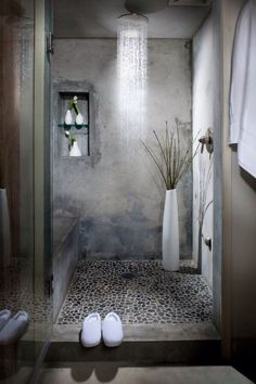 Overhead rain shower, pebble tile floor, cement grey palette, plant or greenery in slender tall vase