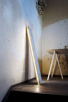 Plank light fixture by Northern Lighting of Norway. The design transforms the ordinary wood plank into a thin, long and simplistic pendant that produces a directed glow that appears generated from the center.