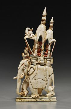 *Antique Indian carved and parcel polychromed ivory model of an elephant; walking and wearing a caparison and elaborate openwork howda with three riders (wear to gilt), late 19th Century.