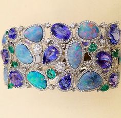 Cellini 's Opal Bracelet accented with Tanzanite , emeralds , and Diamonds on white gold.
