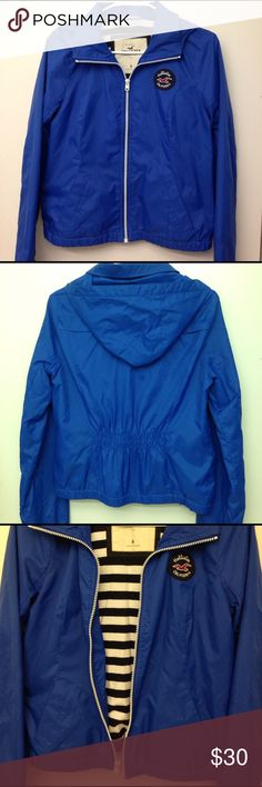 Hollister Windbreaker Blue Hollister Windbreaker Size M but fits on the smaller side (better as size Small). For reference I'm 5'2 and it sits right at my waist. Worn (<20) times but still in excellent condition 9/10. Two close up photos (5-6) show minor flaw, faint brown stains at the top inside lining. Very unnoticeable. Great condition. No trades Hollister Jackets & Coats