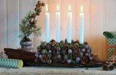 Juledekoration med kogler:Et stykke oasis, Fire lysholdere af metal, Kogler, Ståltråd, Lidt pyntegrønt, Fire kronelys, Et stort stykke bark