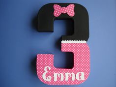 This paper mache number three is painted pink and black on all sides. The front is covered in matching pink polka dot paper. It features white