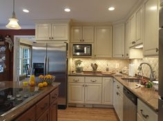 This kitchen I like.  Counters are a bit darker than I wanted but look good with the off-white cabinets.  Backsplash is 4 inch tiles.