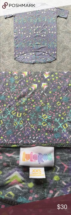 LuLaRoe NWOT XXS Irma T LuLaRoe NWOT XXS Irma T in heathered black with geometric shapes in shades of green, pink, purple, aqua, and white. This design reminds me of the 80s! Smoke free home. LuLaRoe Tops Tees - Short Sleeve