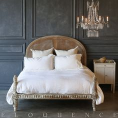 An adorable bed frame finished in a chipping white, revealing wood along the frame's carved details. The rounded cane headboard makes this bed charming and unique.