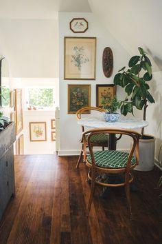 Charming small eating / breakfast nook - Bentwood chairs / vintage art / white walls / dark wood floors