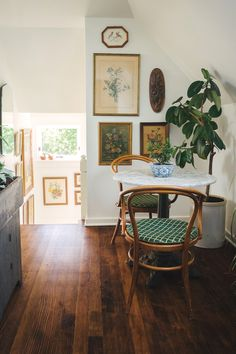 Charming small eating Bentwood chairs / vintage art / white walls / dark wood floors