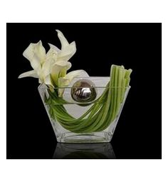 A STAINLESS STEEL FLOATING SPHERE IS ENCIRCLED BY CALLA LILIES SWIRLED WITHIN A CHIC CLEAR GLASS VASE.