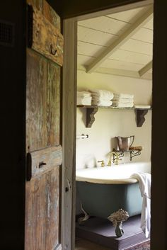 Patrick Dunne's Southern home as featured in Garden and Gun.  I love the claw-foot tub on a pedestal.  I love the rough-finished door and the whitewashed plank ceiling. Would be curious to see the flooring.