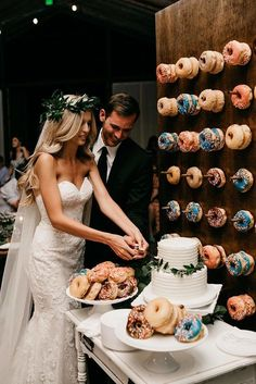 non traditional wedding dessert ideas the groom and the bride cut the cake around the plate with donuts and on the wall donuts luke and mallory via instagram