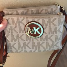 Michael kors cross body purse Small cross body good for traveling. Two zippered pockets and a place in the middle for id and credit cards. Gently used Michael Kors Bags Crossbody Bags