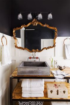 Trinity's husband, Jason, made the vanity with $200 worth of supplies (concrete mix, lumber, and steel piping). An antique mirror, old first aid box, and bamboo purse handles- turned-towel rings are one-of-a-kind fixtures that give the space a collected feel.  I kind of love this sink...