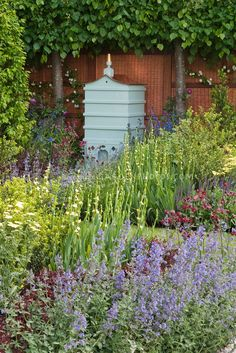 Beehive in beautiful spring garden with bee friendly attracting plants, including Nepeta Formal Garden Design, Bee Boxes, Bee Hives Boxes, Spring Garden, Bee Keeping, Dream Garden, Garden Inspiration, Beautiful Gardens, Outdoor Gardens