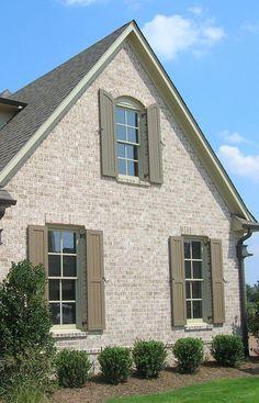 shutters on light brown brick house