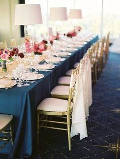 pref. Navy tablecloth with a white and yellow runner. Red roses in vases