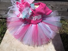 Welcome to This and That Bowtique where you can custom design anything from bows to room décor for your little princess!  This tutu diaper cake contains 1 - 8 oz bottle, 14 - size 1 diapers, 1 - newborn onesie (with your name of choice), 1 - newborn tutu, and 1 - over the top bow on an alligator clip. If you need a different color, please let me know and i will get the colors you need! You can put name, as well as your color choice in the notes when ordering. This is just an example of the…