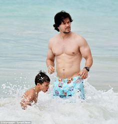 Fit father: The Departed actor showed off his muscly torso as he splashed in the sea with son Michael